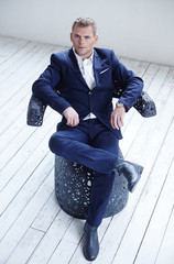 A man in blue suit sitting on black artistic chair.