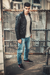 Young stylish man model posing in leather jacket. Agressive style