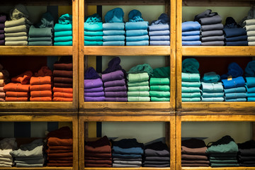 Various color sweatshirts at shelf and shirts on hangers in shop, Italy