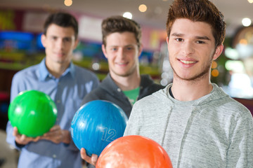 three young men with their bowling ballst