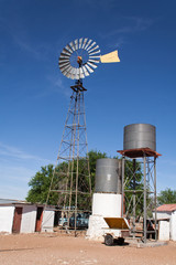 Windmill with water tanks in the desert landscape of Namibia