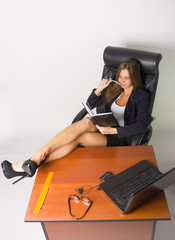 Pretty woman in a business suit sitting at a desk with computer. Studio shot.