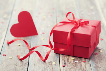 Gift box with red bow ribbon and paper heart on wooden background for Valentines day