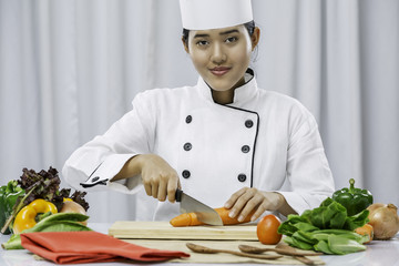 close up of a female chef cutting a carrot and smiling
