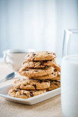 cookies stacked on each other on plate, glass of milk and cup of tea/coffee
