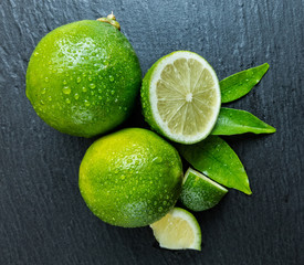 Fresh limes place on black stone
