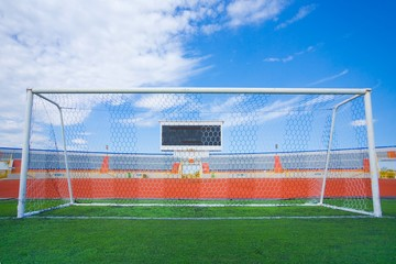 STADIUM - Football field with goal and tablo on blue sky