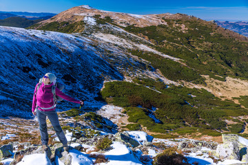 Female Hiker standing on snowy Rocks admiring scenic Winter Mountain View