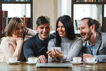 Group of friends with coffee and looking at smartphone