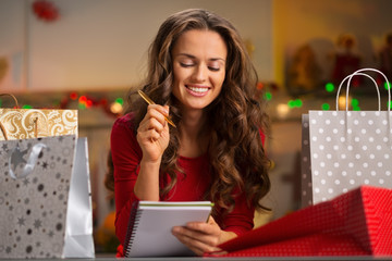 Woman among shopping bags checking list in Christmas kitchen