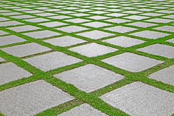 Background of grass between granite stones pathway in garden