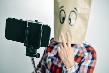 young man with a paper bag in his head taking a selfie