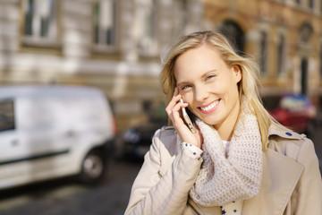 lächelnde frau telefoniert in der stadt