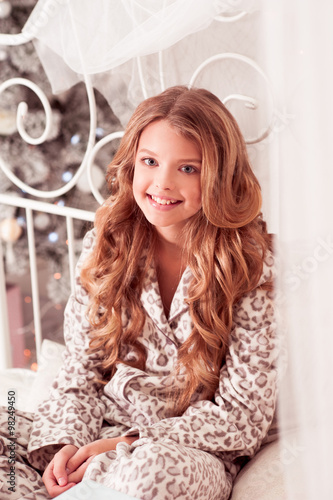 Smiling teen girl 10-12 year old wearing pajamas in room over ...