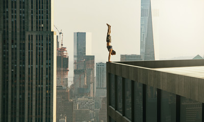 Man performs a handstand on the edge of a skyscraper
