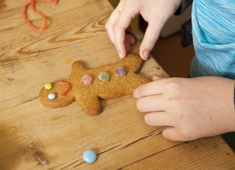 A Gingerbread Man. A  young girl has decorated a gingerbread man with jellies and chocolate sweets.