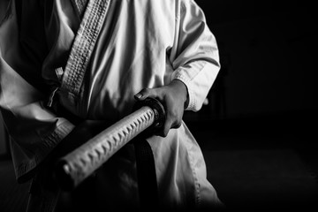 Foto op Aluminium Vechtsport Close up of young martial arts fighter with katana siting in seiza position, black and white.