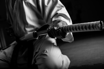 Aluminium Prints Martial arts Close up of young martial arts fighter with katana siting in seiza position, black and white.