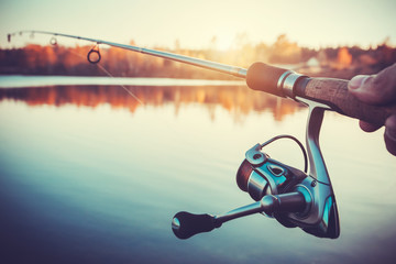 Poster Peche hand with spinning and reel on the evening summer lake