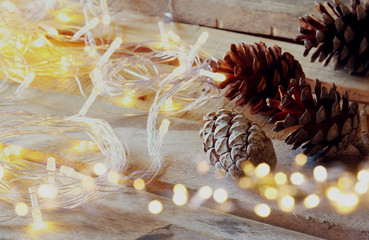 abstract double exposure photo of pine cones next to gold garland lights on wooden background. copy space. retro style filtered