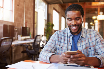 Designer Sitting At Meeting Table Texting On Mobile Phone