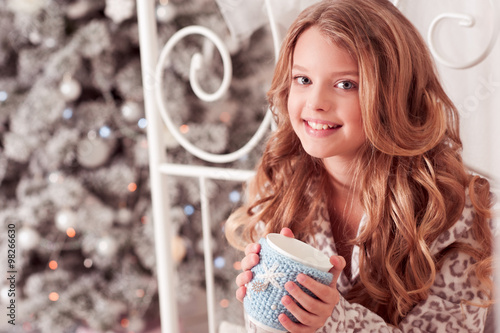 6419131b Smiling kid girl 10-12 year old holding tea cup sitting in bed over  Christmas tree in room. Looking at camera. Celebration. Holiday time.