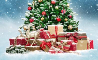 Geschmückter Weihnachtsbaum mit Geschenken im Schnee