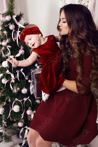725492602e4ba holiday interior photo. beautiful mother having fun with her adorable cute  baby girl,beside Christmas tree