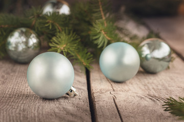 Christmas balls on wooden background with branches of spruce. Decoration.