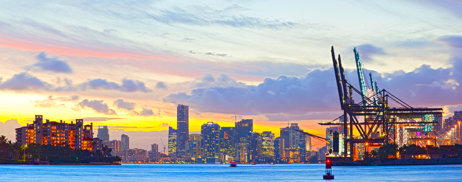 Sunset panorama of Miami Port, Fisher Island and downtown, colorful city light and Biscayne Bay water