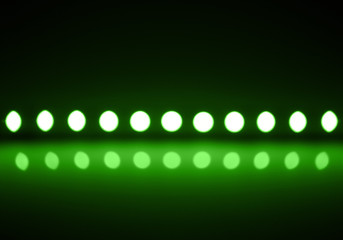 Play of green light on defocusing blur led lamps background