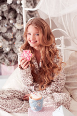 Smiling blonde kid girl eating gingerbread over Christmas tree in room. Sitting in bed. Christmas morning. Looking at camera.