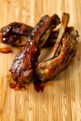 Freshly cooked BBQ ribs with sauce on wooden board
