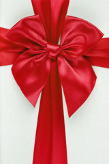 Red ribbon with bow as gift on white background