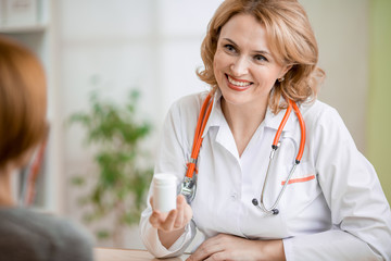 Doctor showing medicine can to patient in her office