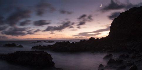 Moonset and sunset at Crescent Bay beach in Laguna Beach, California, United States