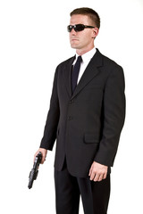 Young man suggesting a secret service agent or secret policeman holding a weapon.