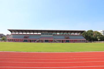 Foto op Plexiglas Stadion Red treadmill, track running at the stadium with green grass on blue sky
