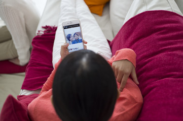 Women are looking at the mobile phone photo gallery on the sofa