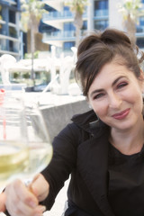 Pretty woman holding glass of wine to camera