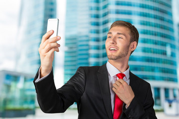 Handsome young businessman taking a selfie with a mobile phone