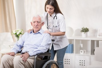 Nurse with old man on wheelchair