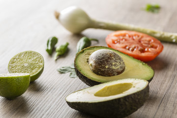 Ingredients for making guacamole on a wooden table