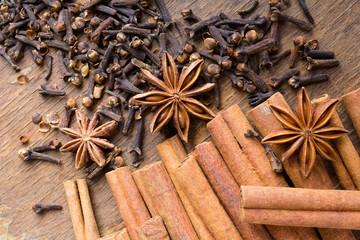Obraz laski cynamonu, gwiazdki anyżu i goździki na drewnianym blacie - fototapety do salonu