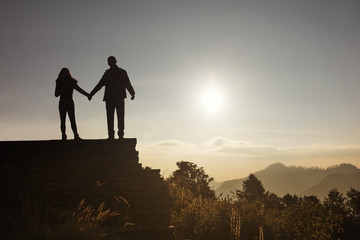 Love couple silhouette looking sunrise in mountains