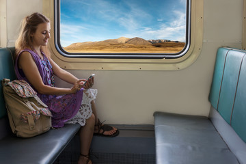 Smiling Girl travel in train in Mountains use Cell Phone to Communicate