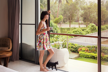 Beautiful Young Woman near big Window with black cat  holding cup and relax inside home