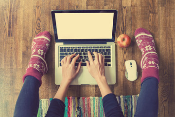 Woman's hands typing on laptop keyboard. Study and work online, freelance, worm socks, winter, home comfort and relax