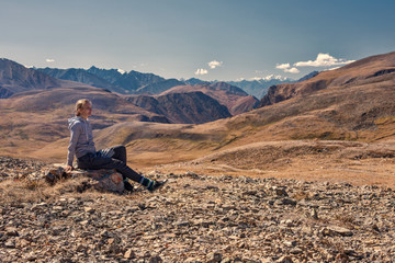 Woman hiker sitting on mountain top, Relax and Enjoy