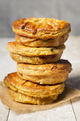 Stack of homemade meat pies on a rustic table
